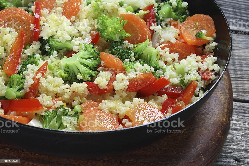 Millet fried with carrots, broccoli, paprika and onion stock photo
