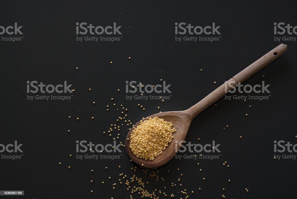millet on wooden spoon on dark wooden table stock photo