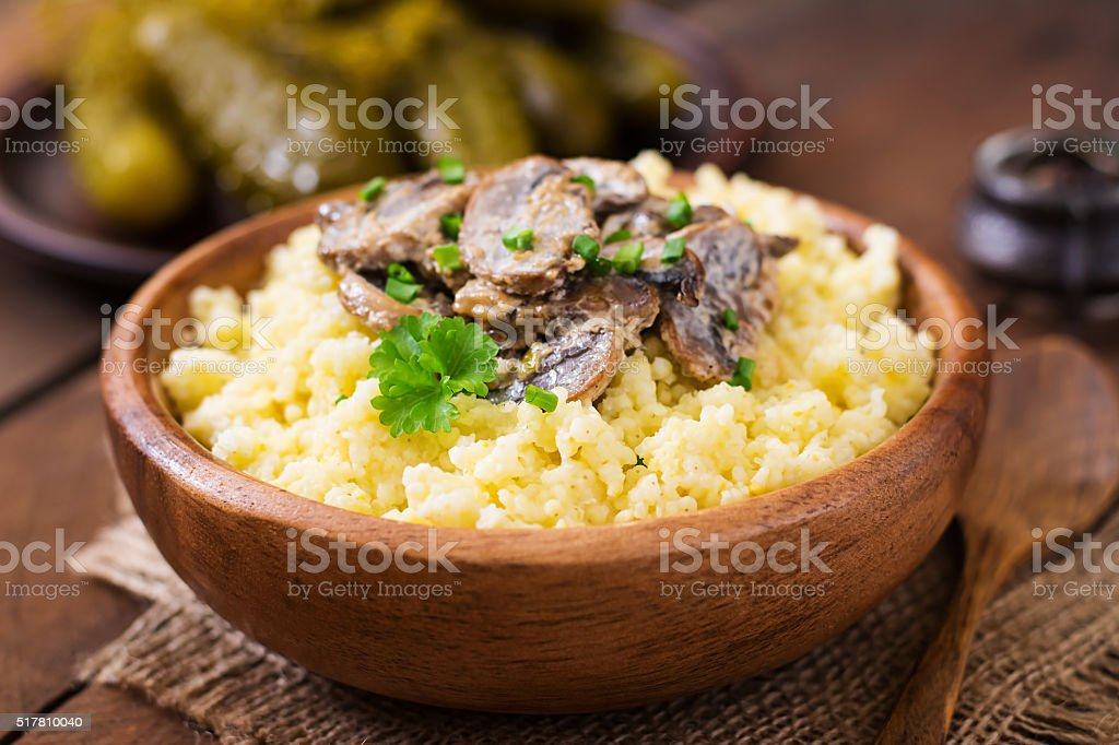 Millet porridge with mushrooms in a wooden bowl stock photo