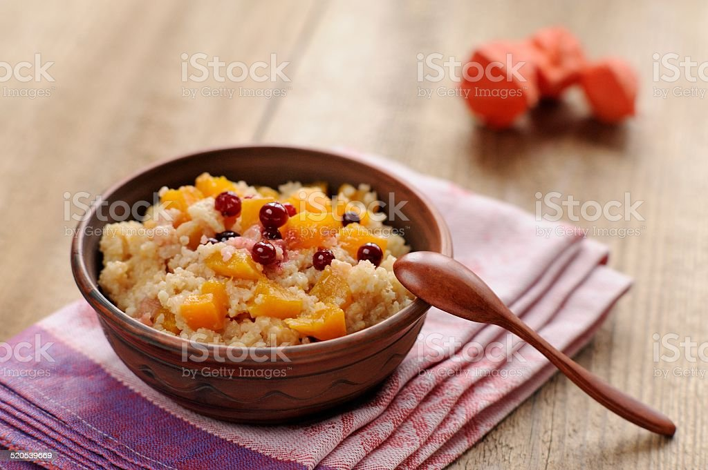 Millet porrige with pumpkin in clay bowl with wooden spoon stock photo