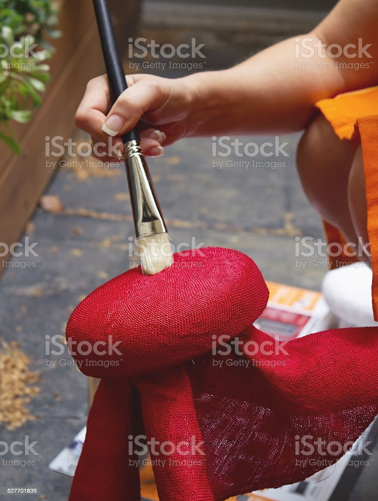 Milliner brushing stiffening solution onto hat block stock photo