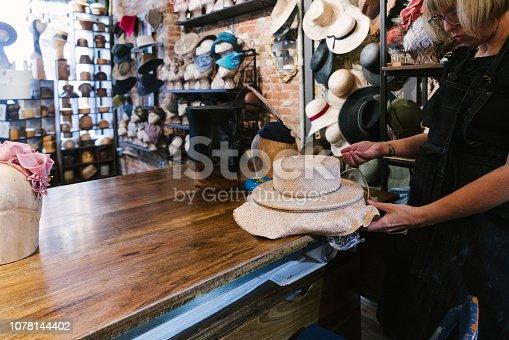 Milliner making handmade customized hats in her workshop.