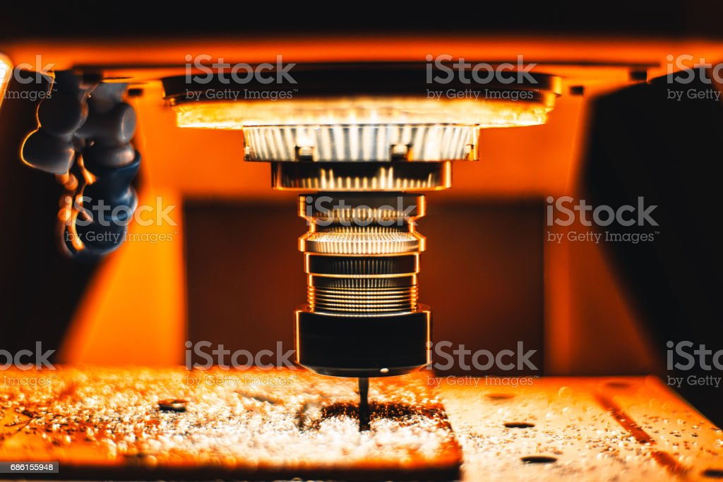 Milling CNC maching in strong orange light Close-up view of manufacturing process with drill cutter of CNC milling machine in strong orange illumination with a lot of metalworking chips around rotating tool on moving table 3D Scanning Stock Photo
