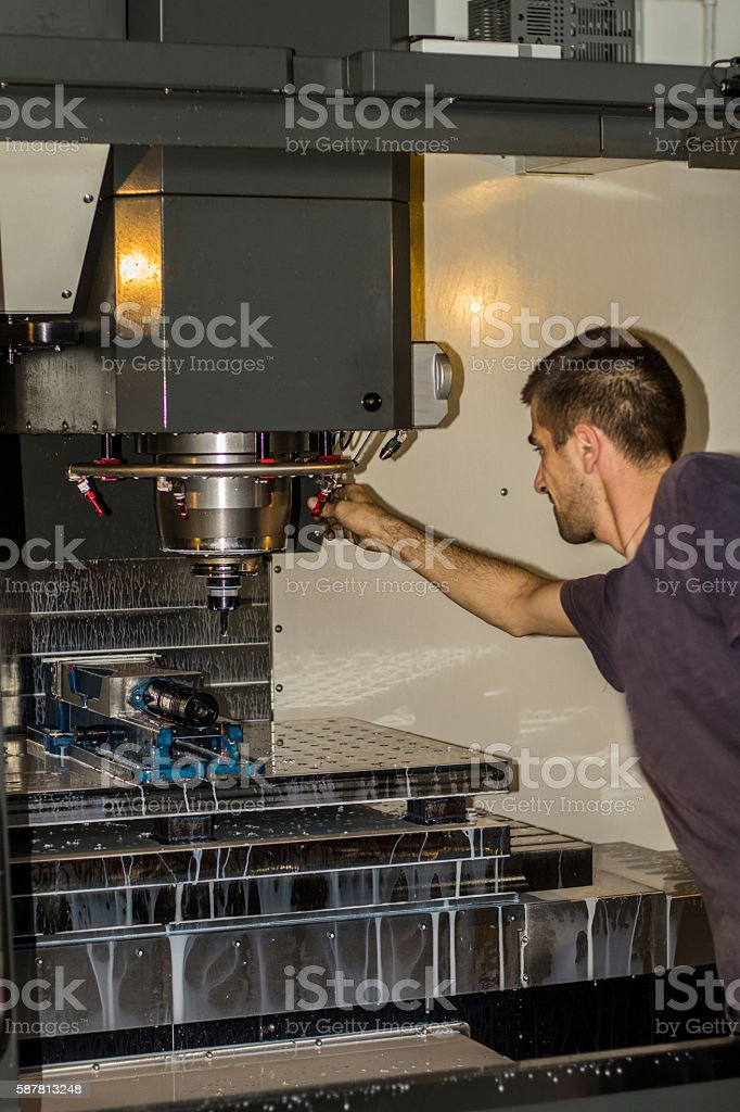 CNC milling machine operator at tool workshop. stock photo