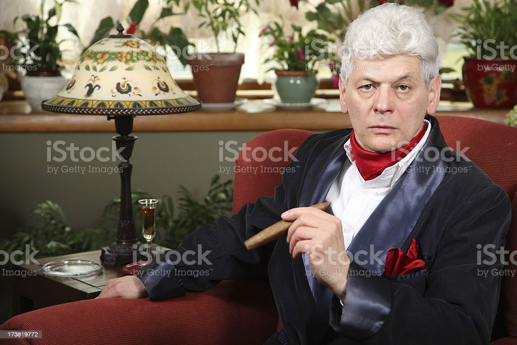 Millionaire at home with smoking jacket, cigar, and intense look stock photo