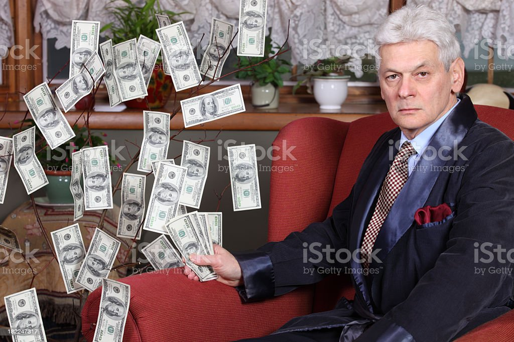 Millionaire sitting next to and holding cash from money tree stock photo