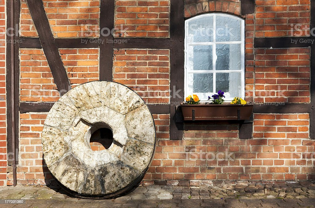 Millstone in front of half-timbered house stock photo