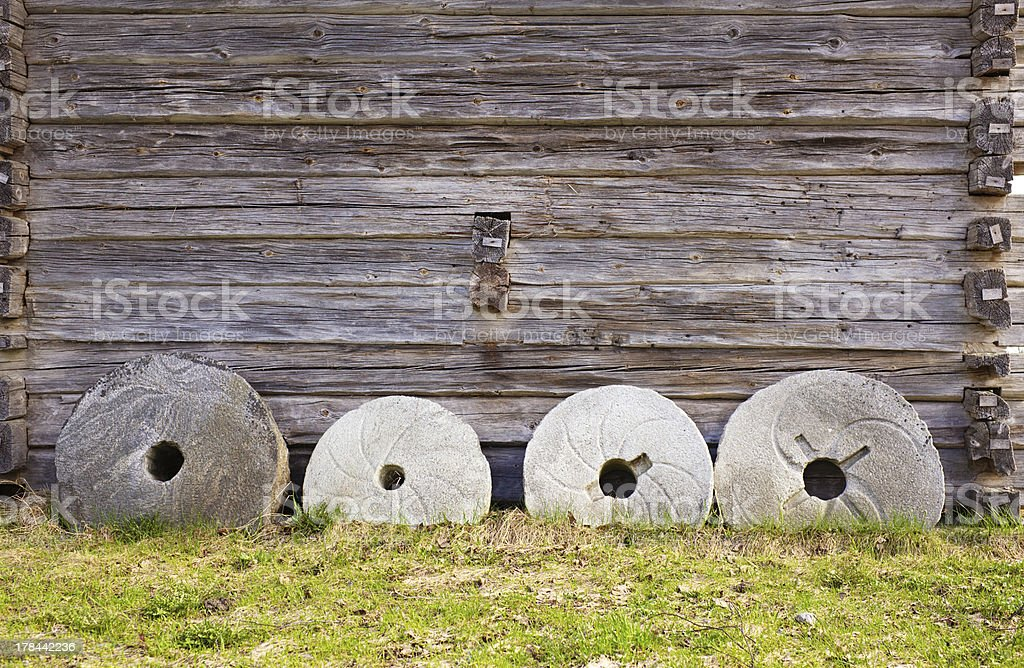 Millstones against wall stock photo