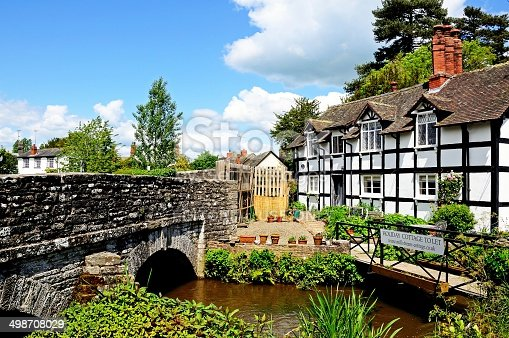 Eardisland, United Kingdom - June 5, 2014:  View of the black and white timbered Millstream cottage alongisde a stream which is used for holiday lettings, Eardisland, Herefordshire, England, UK, Western Europe.
