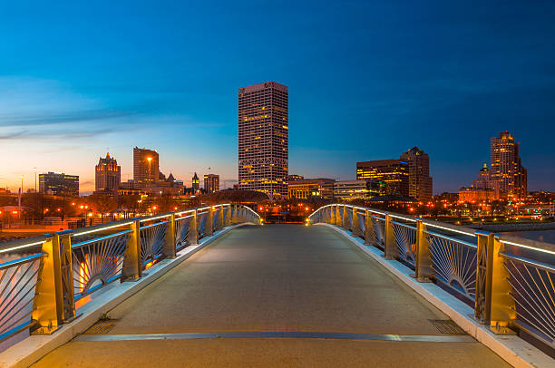 Milwaukee skyline at dusk from a pedestrian bridge Downtown Milwaukee skyline at dusk from a footbridge in Lakeshore State Park (on the Hank Aaron State Trail.)  Perspective / Horizon effect used. milwaukee wisconsin stock pictures, royalty-free photos & images