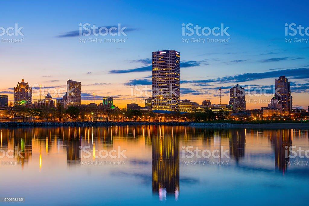 Milwaukee skyline with mirrorlike lake reflections and blue/orange/peach sunset stock photo