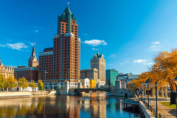 Milwaukee skyscrapers and river with Autumn trees Downtown Milwaukee skyscrapers (prominently showing Milwaukee Center) with the Milwaukee River and orange colored trees during Autumn in the foreground. milwaukee wisconsin stock pictures, royalty-free photos & images