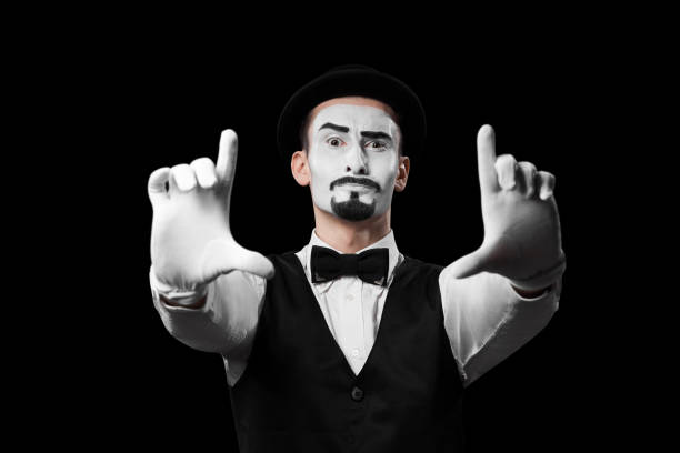 Mime artist showing frame sign with hands isolated on black background. stock photo