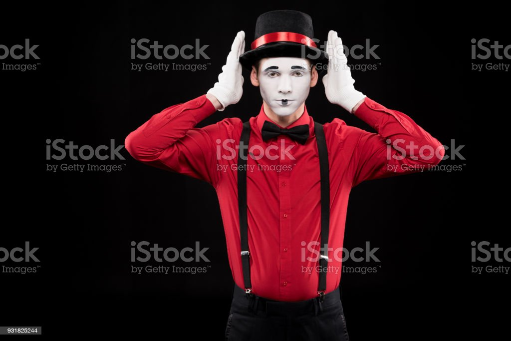 mime covering ears with hands isolated on black stock photo