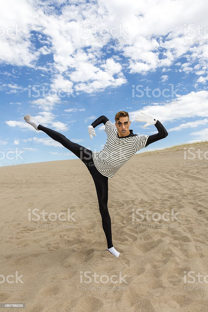 Mime doing a one leg high kick in the desert stock photo