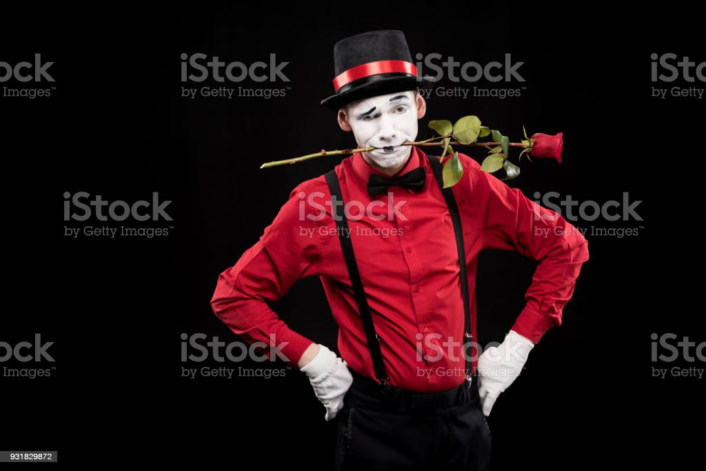 mime grimacing and holding red rose in mouth isolated on black stock photo