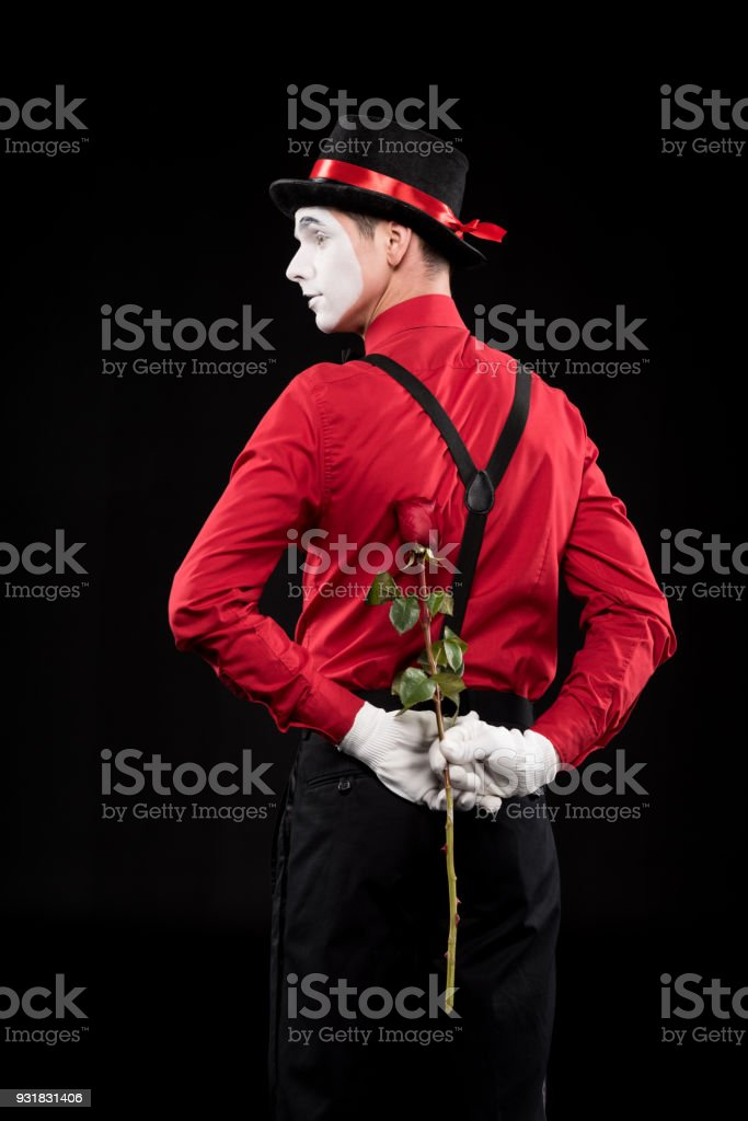 mime hiding rose behind back isolated on black stock photo