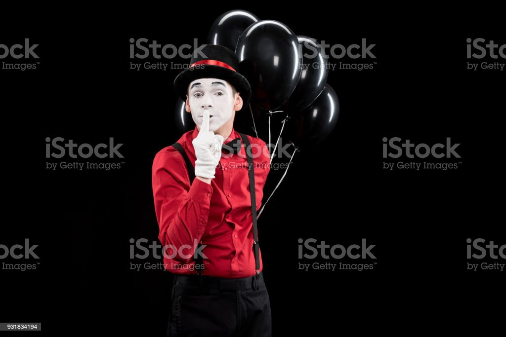 mime holding balloons and showing silence sign isolated on black stock photo