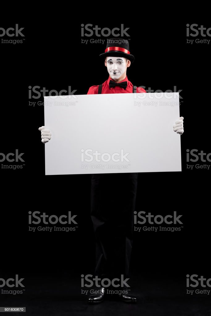 mime holding empty board isolated on black stock photo