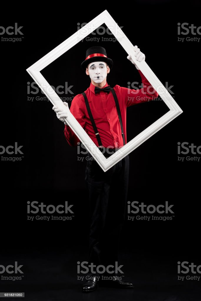 mime holding frame and looking at camera isolated on black stock photo