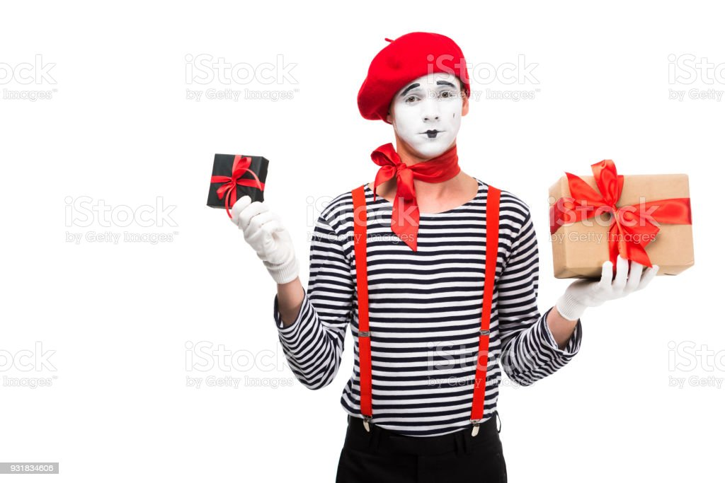 mime holding present boxes and looking at camera isolated on white stock photo