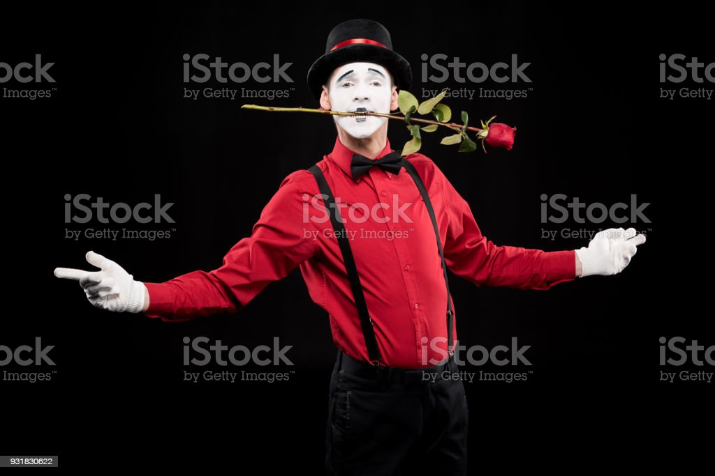 mime holding red rose in mouth and standing with open arms isolated on black stock photo