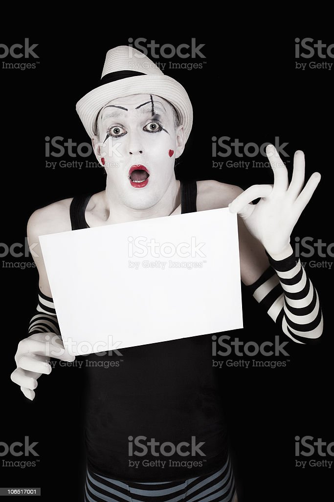 mime in striped gloves and hat, holding a white blank royalty-free stock photo