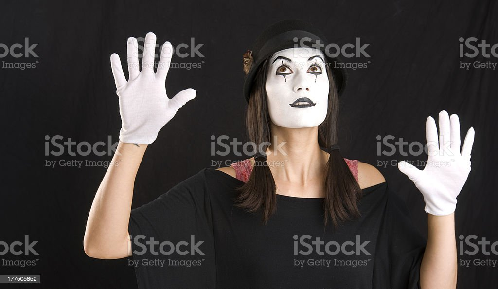 Mime Looks and Holds Hands Up in White Face royalty-free stock photo