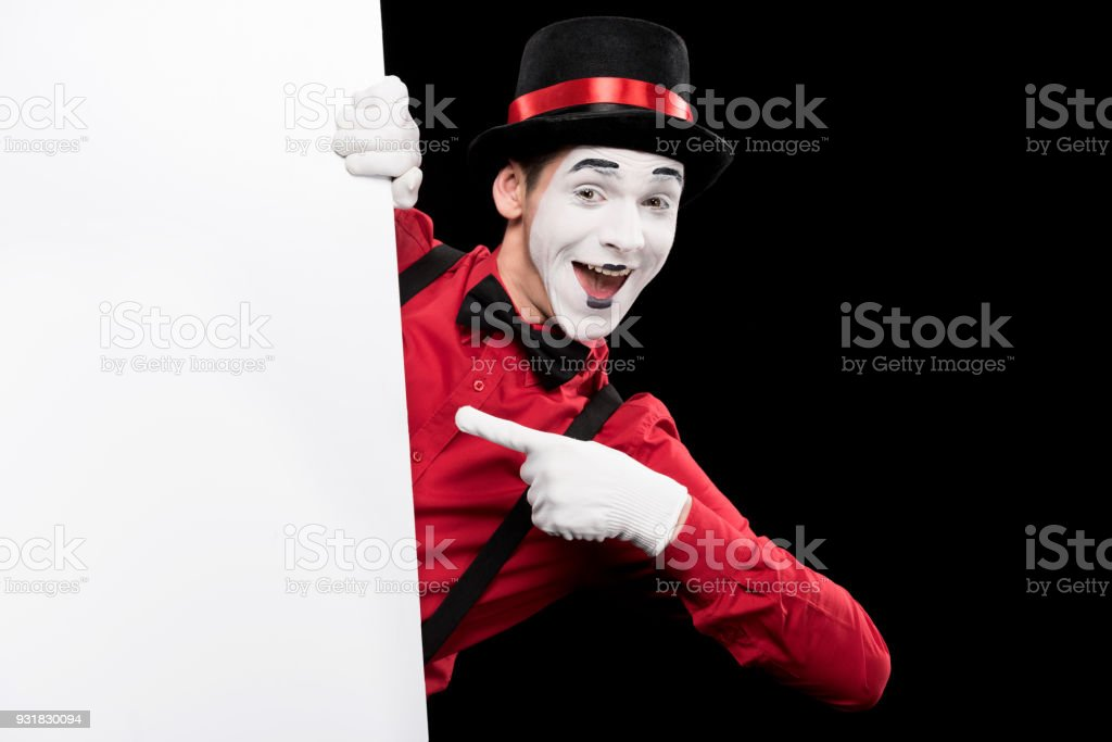 mime pointing on empty board isolated on black stock photo