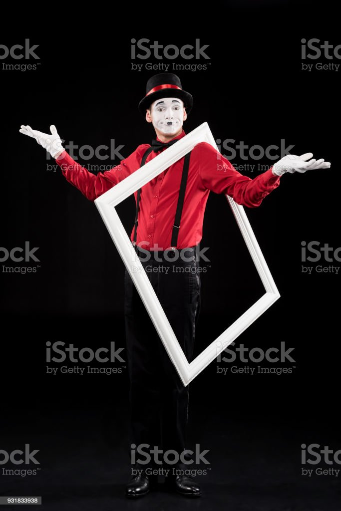 mime showing shrug gesture and holding frame on shoulder isolated on black stock photo