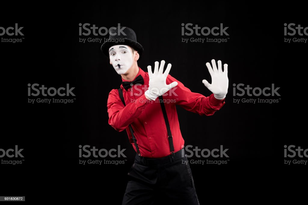 mime showing stop sign isolated on black stock photo