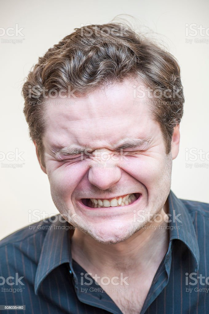 Mimicry of depressed, angry, screaming, curly man on white background stock photo