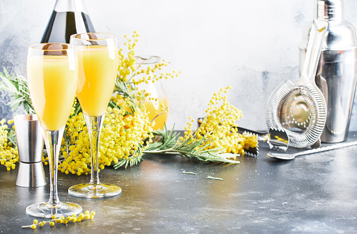 Mimosa alcohol cocktail with orange juice and cold dry champagne or sparkling wine in glasses, gray bar counter background with yelow flowers, copy space, selective focus