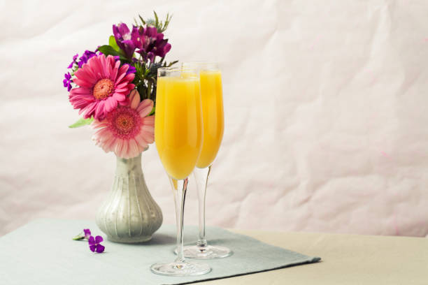 Mimosa cocktail and flowers stock photo