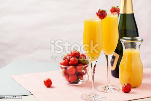 Two glasses of mimosa cocktail (champagne with orange juice) and fresh strawberries