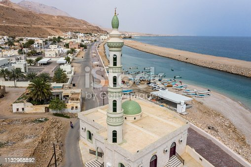 Small town mosque with a single minaret, towering over a small town of Tiwi in Oman. Gulf of Oman is visible in the back.