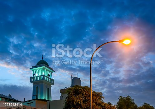 Mosque Tower lit in green against a blue evening sky alongwith a brightly lit yellow streetlight. From Muscat, Oman.