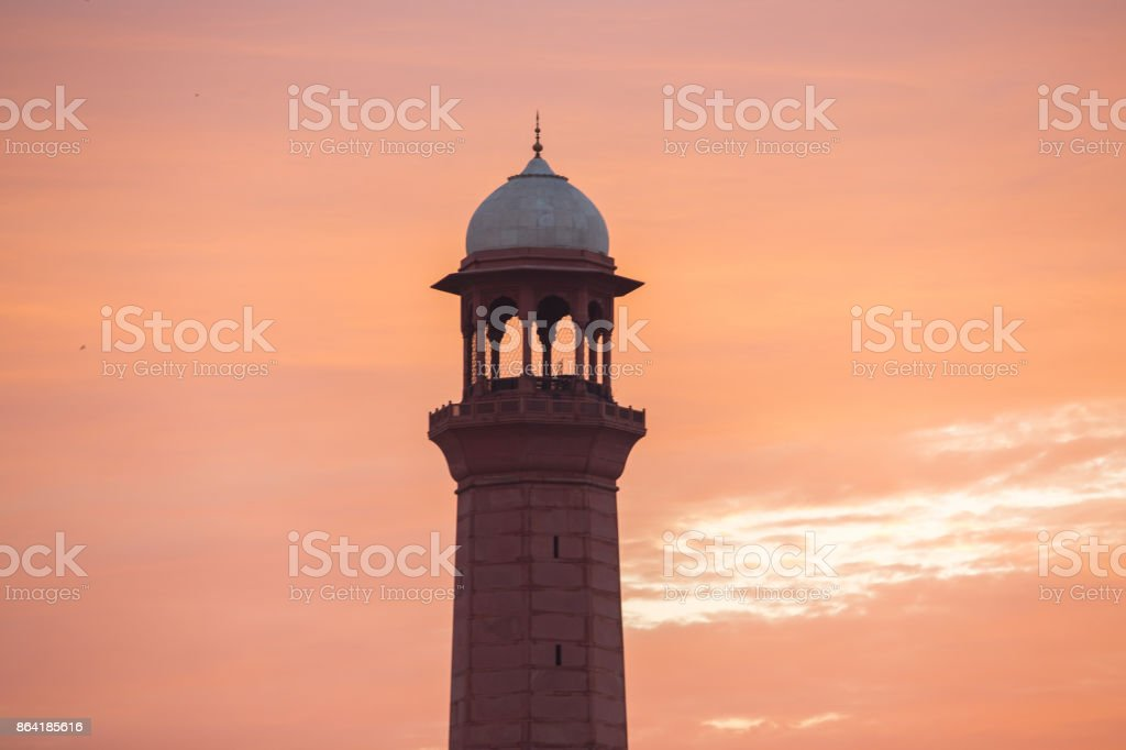 Minaret tower of a mosque calling for prayers in fiery sunset sky royalty-free stock photo