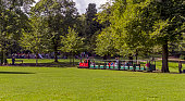 Buxton, UK - September 2, 2015: View of a minature steam train in the Pavilion gardens, Buxston, Derbyshire.  People can be seen riding on the train, walking and playing in the park.