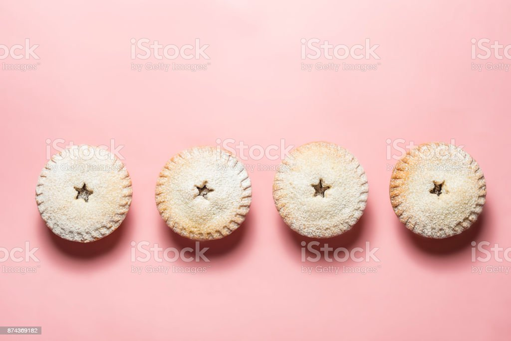 Mince pies against a Pink background. stock photo