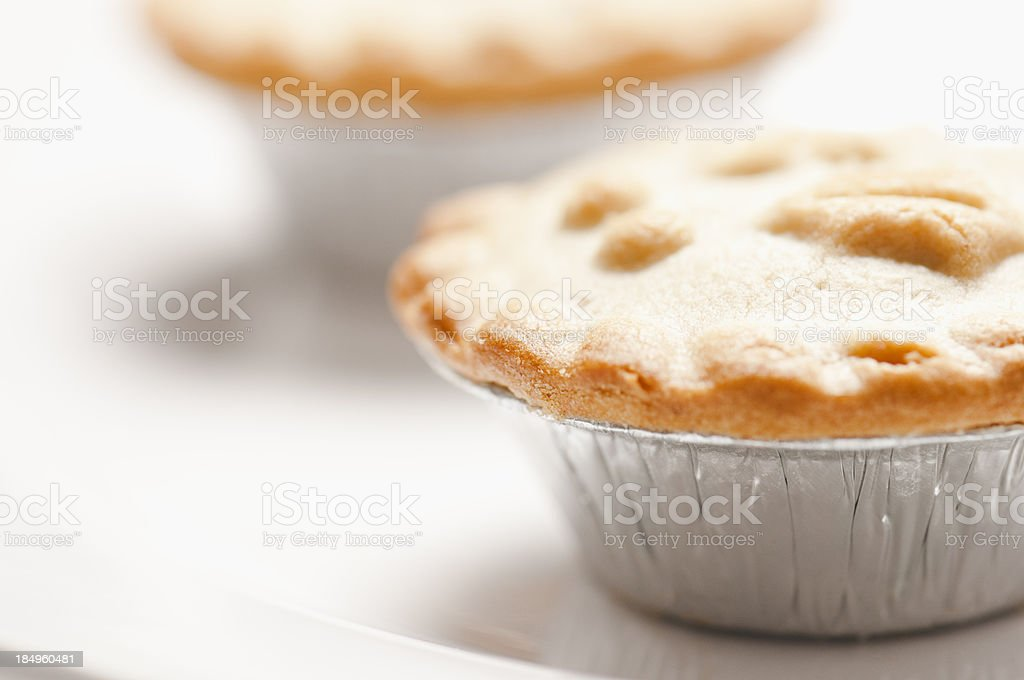 Mince pies in silver foil wrappers on white plate stock photo