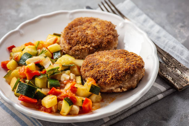 Minced beef cutlets served with and stewed vegetables. stock photo