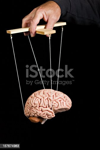 Brain suspended from puppet strings. A concept shot for all forms of mind control. Shot on a black background.