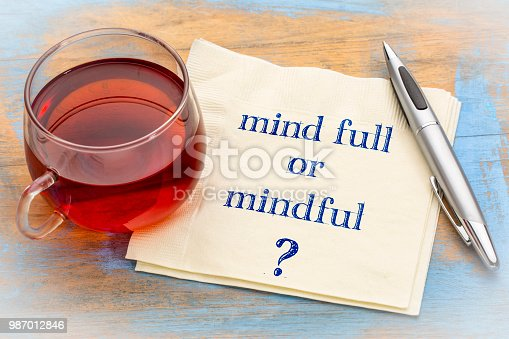 Mind full or mindful ? Inspiraitonal handwriting on a napkin with a cup of tea.