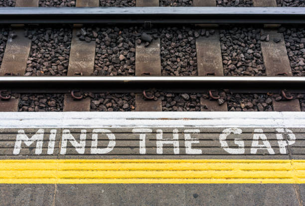mind the gap teken op een london underground station-platform - kloof stockfoto's en -beelden