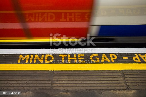Yellow MIND THE GAP sign at the London subway platform. Turist atraction.