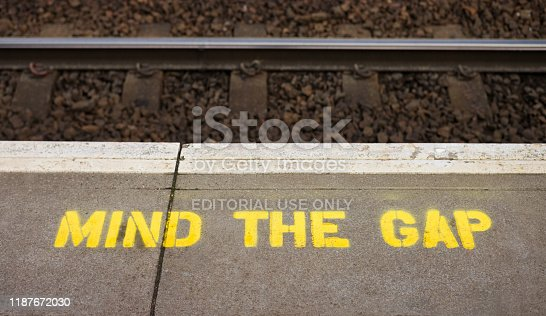 Close-up of a 'Mind The Gap' sign painted on a station platform, warning passengers to avoid the gap between the platfrom and trains.