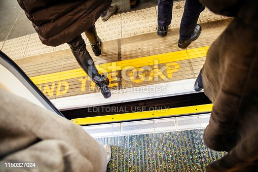 London: Directly above view at Mind the gap sign in London Underground metro train station with feets of pedestrians exiting entering metro train