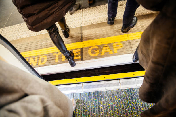 MInd the gap yellow sing in London Tube underground metro London: Directly above view at Mind the gap sign in London Underground metro train station with feets of pedestrians exiting entering metro train apart stock pictures, royalty-free photos & images