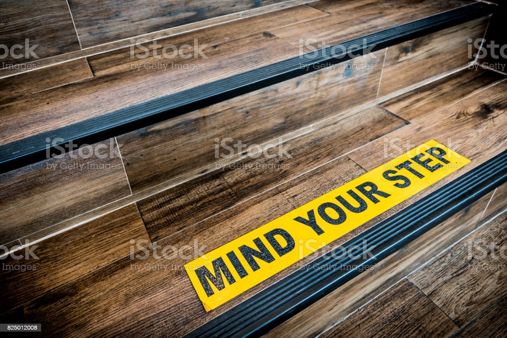 Mind your step sticker sign pasted on wooden stair. Warnings, abstract, or indoor architecture concept stock photo